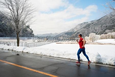 male runner running along road in