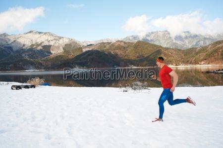 male runner running along snow covered