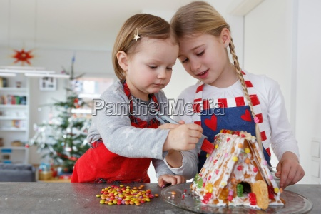 girls at kitchen counter decorating gingerbread