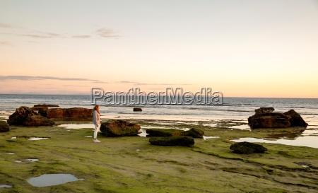 woman watching sunset from rocky beach