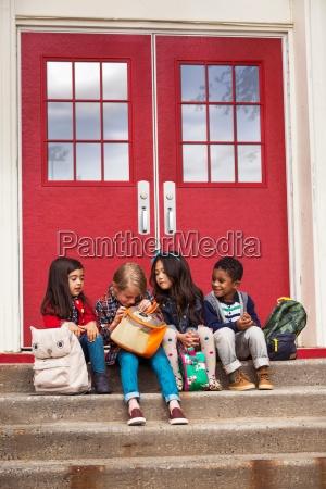 elementary schoolgirls and boys sitting on