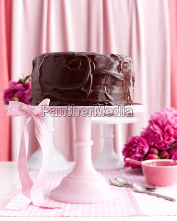 chocolate layer cake on pink stand