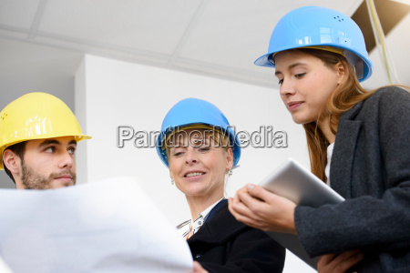 businesswoman questioning blue print in new