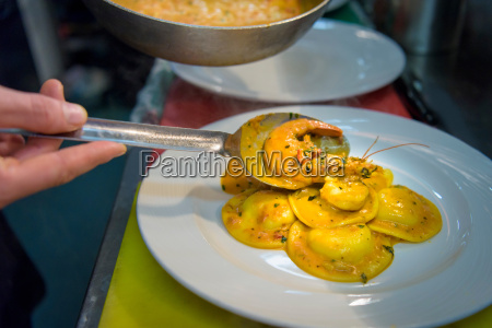 chef plating up lobster ravioli in