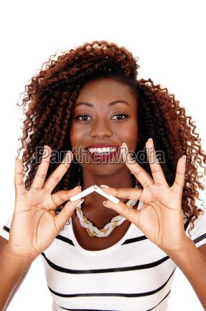 black woman breaking cigarette