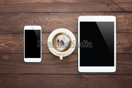 white phone tablet and coffee cup