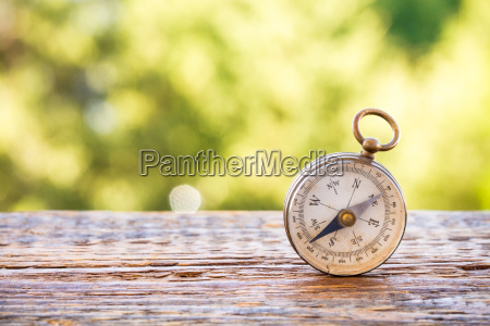 vintage compass on wooden table and