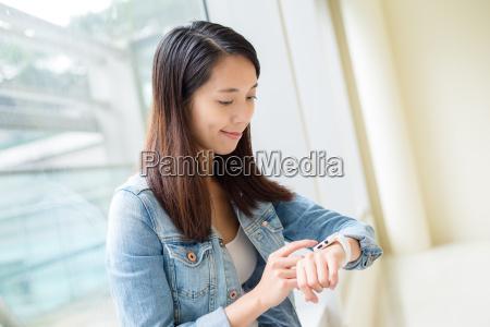 asian woman using wearable smart watch