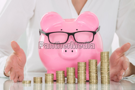 females hand protecting piggybank and stacked