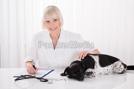 female veterinarian writing prescription for dog
