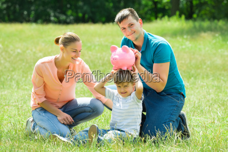 parents with their son holding piggy