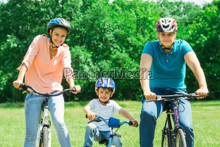 happy family cycling in park