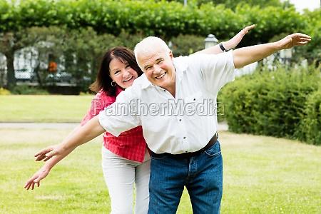 senior couple making flying gesture