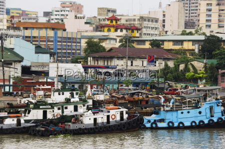 barges on river pasig with city