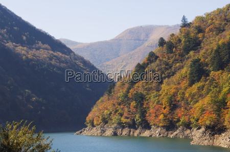 reservoir surrounded by mountains with autumn