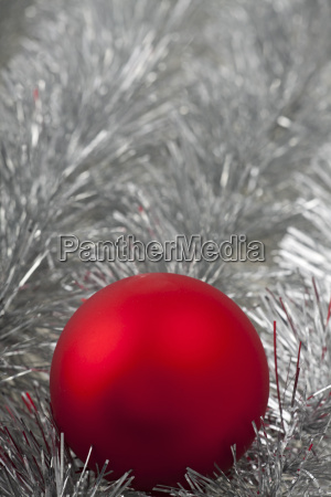 red christmas ball on silver tinsel