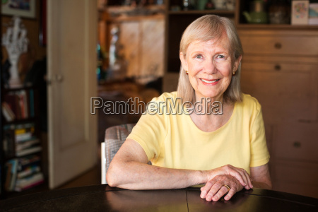 confident mature woman seated at table