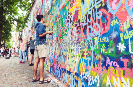 young man painting grafitti wall
