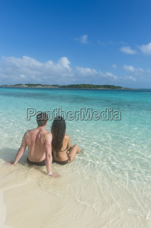 couple sitting on a white sand