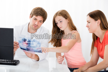 doctor showing teeth xray to mother