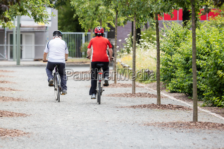 rear view of couple riding bicycle