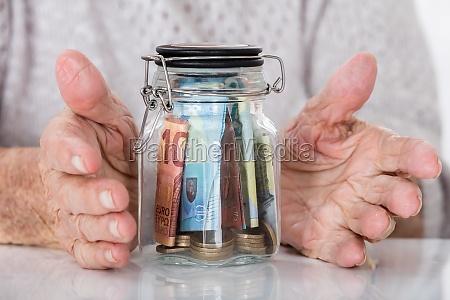 senior womans hand protecting money jar