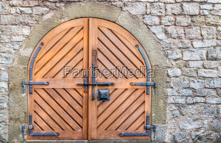 double wooden door and stone wall
