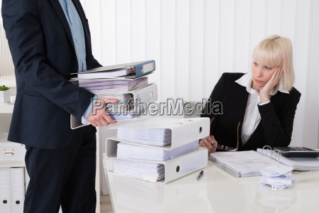 businessman giving pile of folders to
