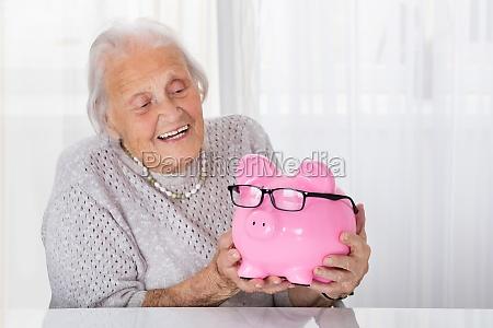 senior woman holding piggybank