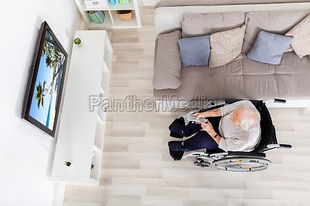 elder woman watching movie on television