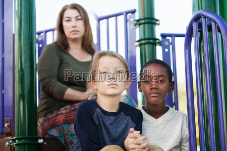 two boys sitting with mother at