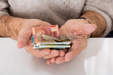 senior woman showing money on palm
