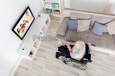 handicapped grandmother watching television at home