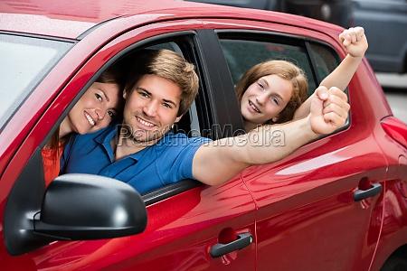 family sitting in car raising their