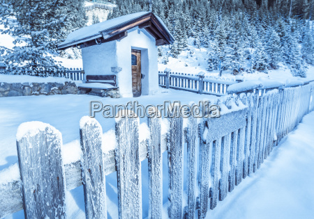 frozen wooden fence and rustic chapel