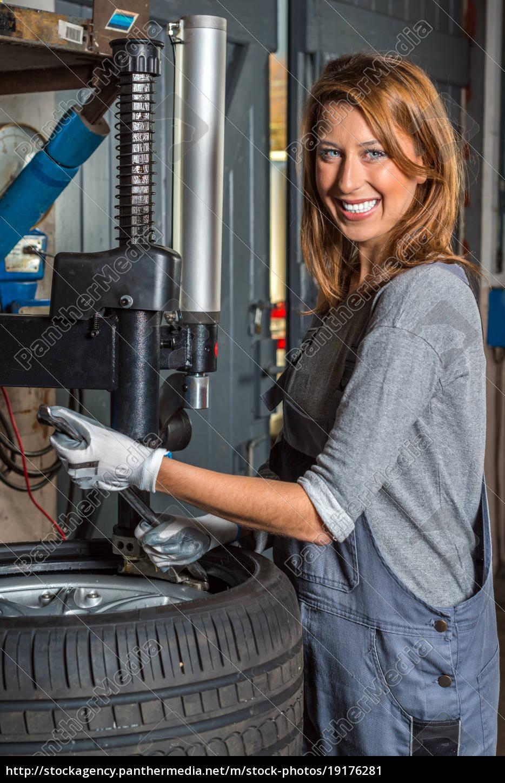 female, mechanic, changing, car, tire. - 19176281