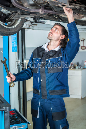 mechanic, repairing, a, lifted, car, with - 19176333