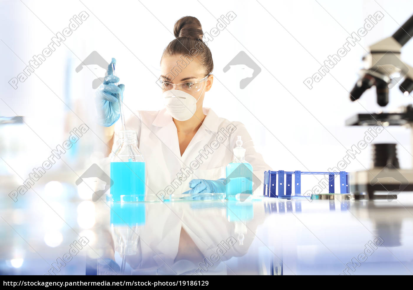 the, chemist, examines, the, sample, under - 19186129