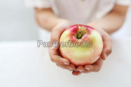 dziecko trzyma w dloniach jablko