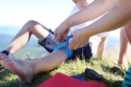 mother provides children knee elastic bandage