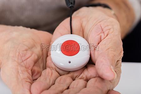 senior woman holding alarm button