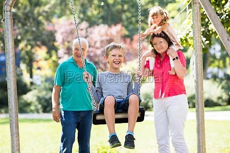 grandson enjoying on swing in the