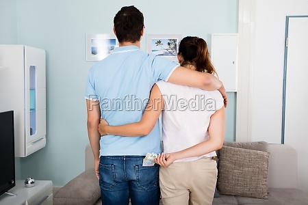 woman stealing money from husbands pocket