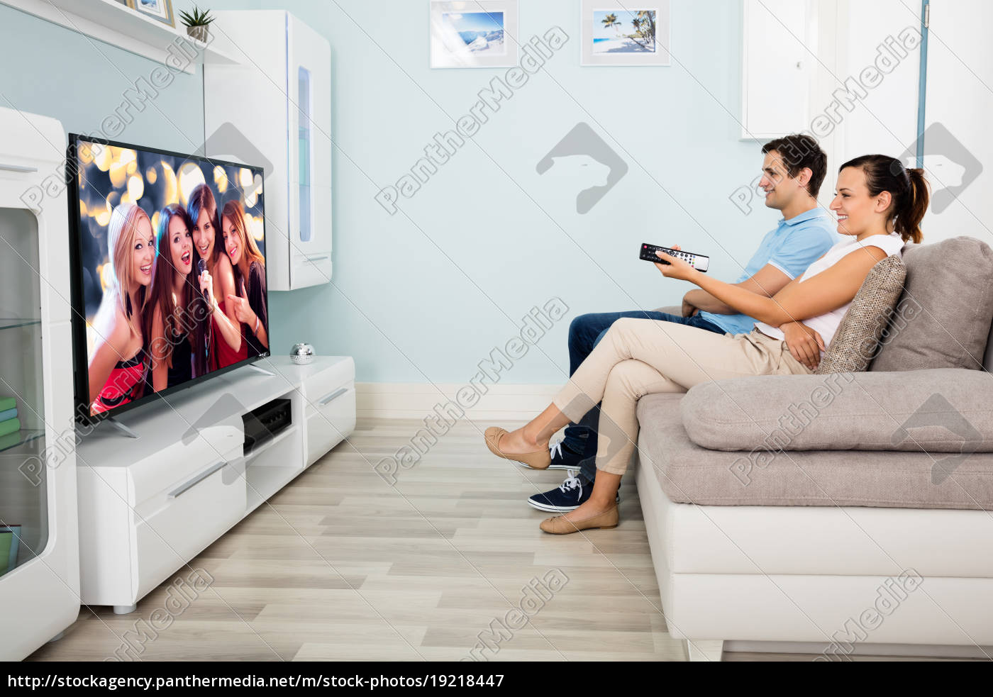 couple, sitting, on, sofa, watching, television - 19218447