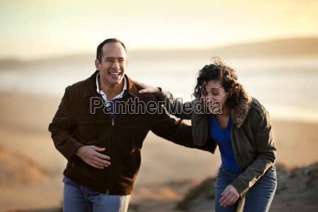 laughing mid adult couple standing together