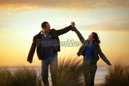 happy mid adult couple holding hands