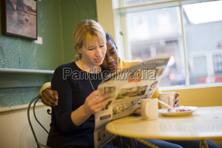 two women reading a newspaper at