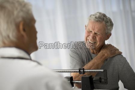 mature man grips his shoulder in