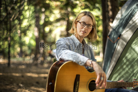 mid adult woman playing guitar while