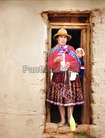 peruvian woman in doorway with child